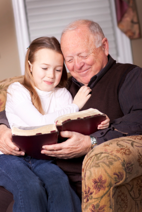 Grandpa reading the Bible to his granddaughter