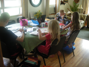 My kids doing their notebook pages (what a mess!)