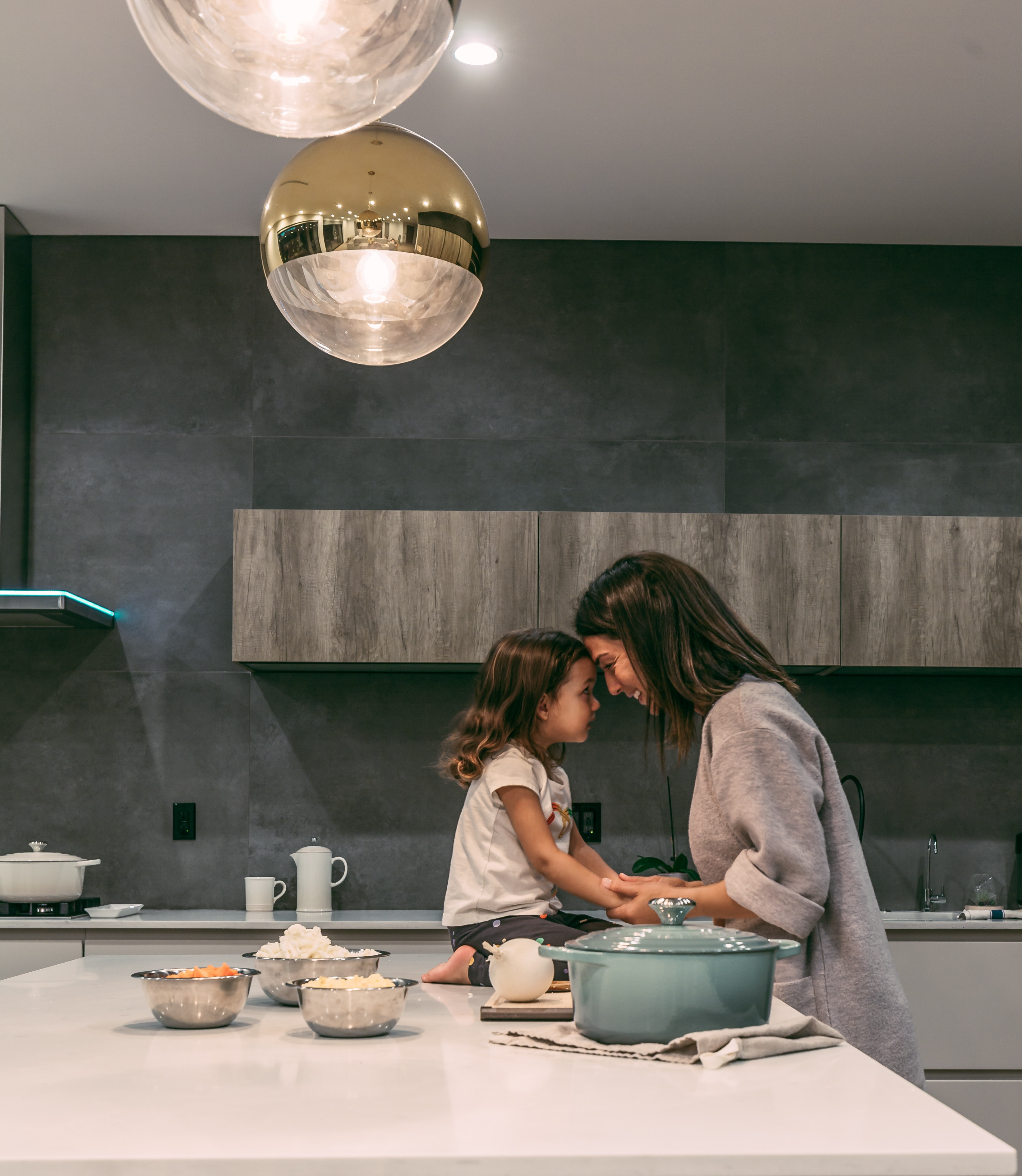 A mom snuggling with daughter in kitchen