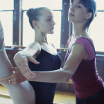 Instructor Lifting Ballet Dancer's Leg