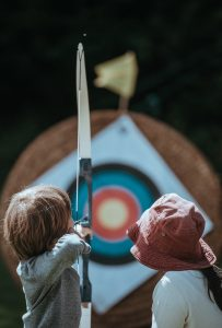 A mother teaches her son to shoot an arrow | Photo by Annie Spratt on Unsplash.