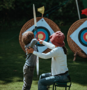 mother pointing her son to shoot an arrow straight